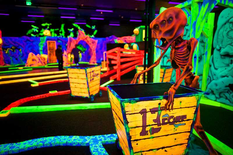 by: TIMES PHOTO: JAIME VALDEZ - Aliens seem to take their positions at the Glowing Greens Blacklight Mini Golf Alien Invasion course on Southwest Murray Boulevard.