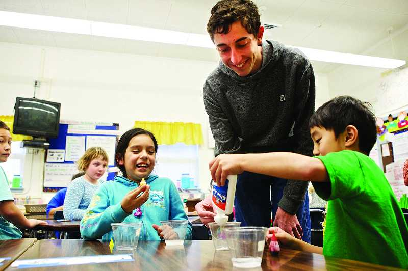 by: TIMES PHOTO: JAIME VALDEZ - Westview High School senior Chris Younkins helps Giselle Miranda and Trung Pham combine ingredients to make a rubber ball in his Science Stars program at McKay Elementary School.