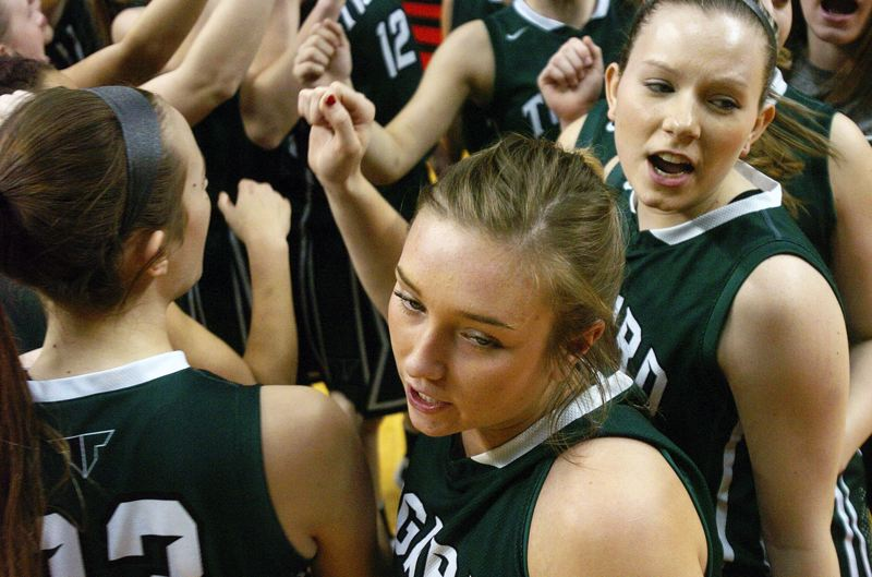 by: DAN BROOD - TOGETHERNESS -- The Tigard girls basketball team, including junior Faithe Wantland (center) and senior Hannah Armstead (right) gather just prior to the opening tip of the state tournament quarterfinal contest.