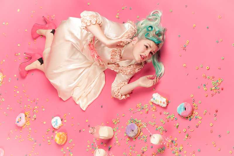 by: COURTESY OF RAINA STINSON PHOTOGRAPHY - Another photo in Raina Stinson's award-winning series is 'Doughnut Madness,' featuring Malia Rodgers, a Tualatin High School senior surrounded by a flurry of pastel doughnuts and a scattering of confetti-like cereal bits.