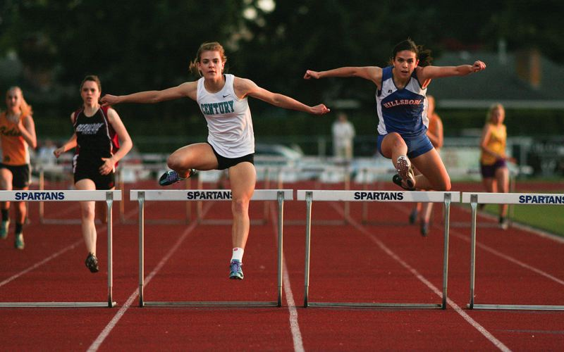by: HILLSBORO TRIBUNE PHOTO: AMANDA MILES - Hillsboro's Sami Moellmer and Century's Braana Weber go stride-for-stride in the girls 300-meter hurdles at last year's Elden Kellar Invitational track and field meet.
