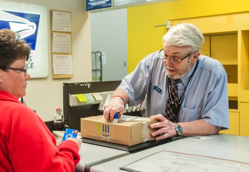 by: SPOKESMAN PHOTO: JOSH KULLA - Wilsonville Post Office employee Steve Sanks stamps a package. He has been a fixture behind the counter since the Wilsonville facility opened in 1994. He retires March 31.