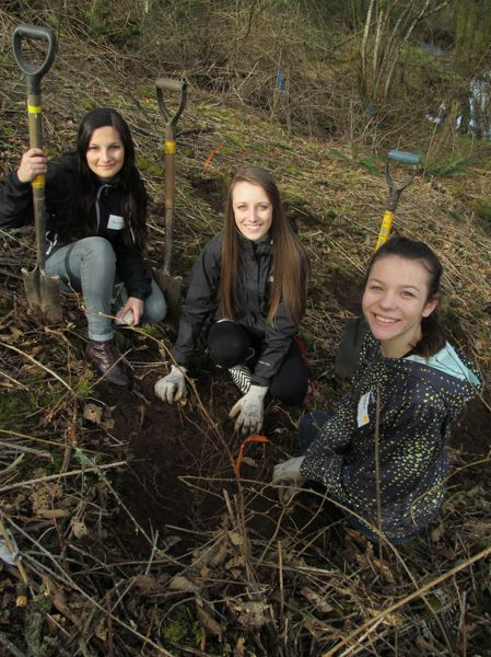 by: PHOTO BY ELLEN SPITALERI - From left, Evelina Bosovik, Yuliya Nikiforets and  Alina Kulyak get ready to plant native seedlings.