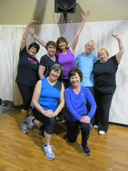 by: PHOTO BY ELLEN SPITALERI - Members of the cross-training class at Abernethy Performing Arts surround instructor Shirley Hall, center, with arms outstretched.