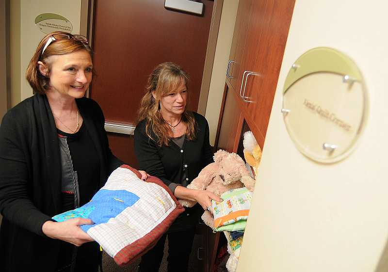 by: PAMPLIN MEDIA GROUP: VERN UYETAKE - Executive Director Barbara Peschiera, left, and interviewer Sue Lewis show some of the items in the center's quilt corner, where each child seen is allowed to choose a quilt and a teddy bear to keep.