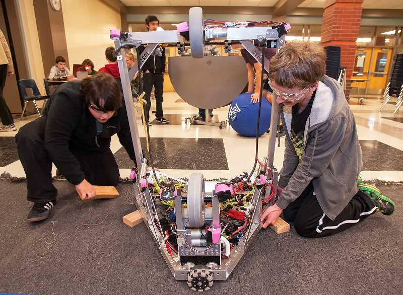 by: SPOKESMAN FILE PHOTO: JOSH KULLA - Adrian Shotola-Hardt, left, and Kjel Petterson-Willey fine-tune FIRST Team 1425's robot ahead of the regional competition at Wilsonville High School March 21 and 22.