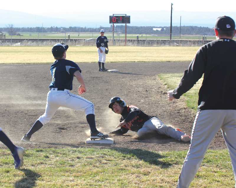 by: JEFF WILSON/THE PIONEER - Culver's Joe Daugherty slides safely into third base during the Bulldogs' season opening baseball series against La Pine last week. Daugherty had three extra-base hits in the two games.