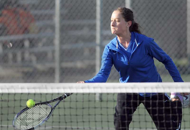 by: SETH GORDON - Net play - Morgan Johnson lunges for a volley during her 6-1, 6-1 victory over Glencoe's Anna Shapland at No. 4 singles March 20 at Newberg High School. The Tigers swept the Crimson Tide 8-0.