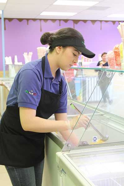 by: LINDSAY KEEFER - Alondra Martinez, an employee at El Paisanito, spoons out a raspados treat for a customer.
