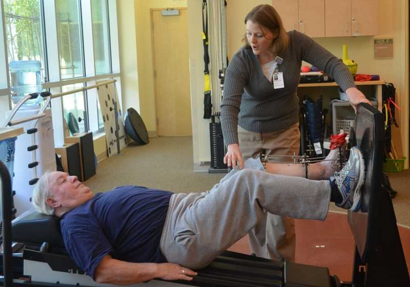 by: JANIS BRENTANO - Bill Leder works with physical therapist Robyn Tynan at Woodburn Health Center to strengthen his left leg after a tractor accident left him severely injured six months ago.