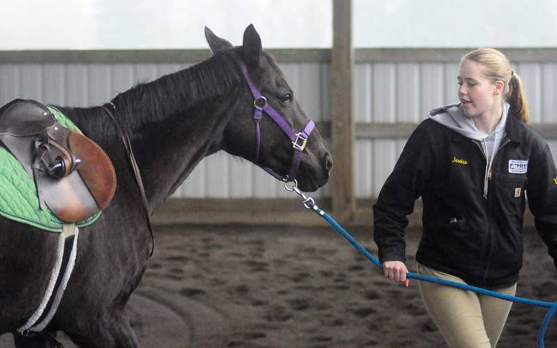 by: PAMPLIN MEDIA GROUP: MATT SHERMAN - Jessica Hughes leads her horse, Lady, on a course set up in Wilsonville.