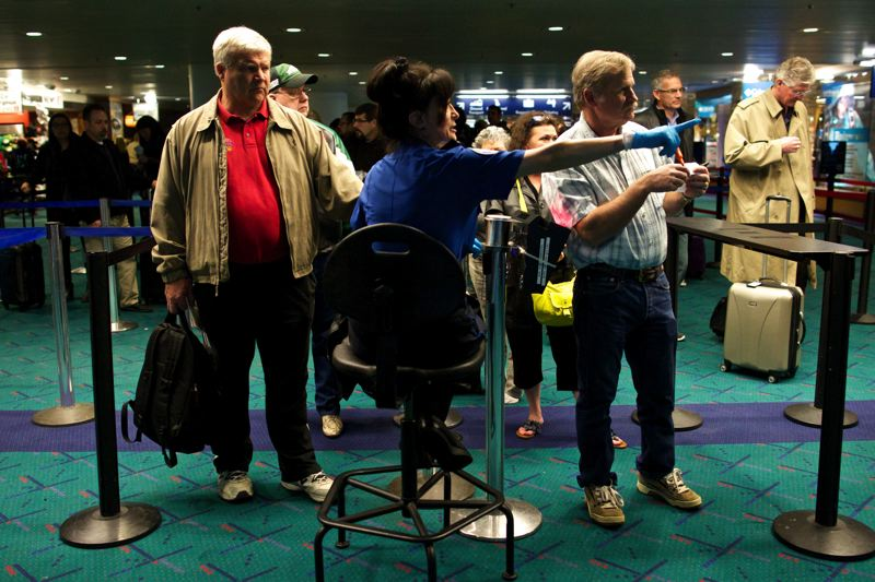 by: TRIBUNE PHOTO: JAIME VALDEZ - Seated and without the barrier of a podium, Portland TSA Security Officer Kathy Mafi-Henderson is a little less imposing and a little more likely to ratchet down travelers anxiety -precisely what the airport wants, since calmer passengers get through security quicker.