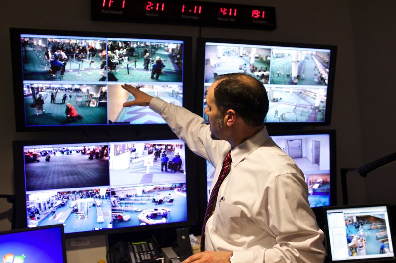 by: TRIBUNE PHOTO: JAIME VALDEZ - Ken Alwine, manager of the Oregon Coordination Center at PDX, points to monitors from cameras located around the terminal. At the first signs of a bottleneck, Alwine can dispense TSA officers to help alleviate the problem.
