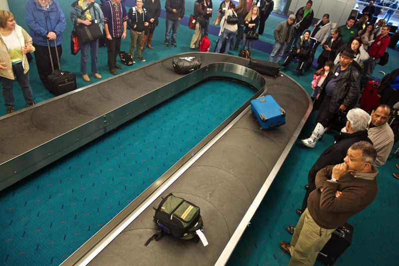 by: TRIBUNE PHOTO: JAIME VALDEZ - If all those travelers waiting for their bags would stand back, the system would operate more efficiently and politely. But they probably won't unless PDX can build into the baggage claim as way of inducing the preferred behavior.