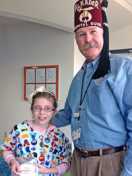 by: SUBMITTED PHOTO: KAY WEBER - Hallinan fourth-grader Annabelle Hay delivered the schools gown donation into the hands of Radiology department manager Scot Duncil.