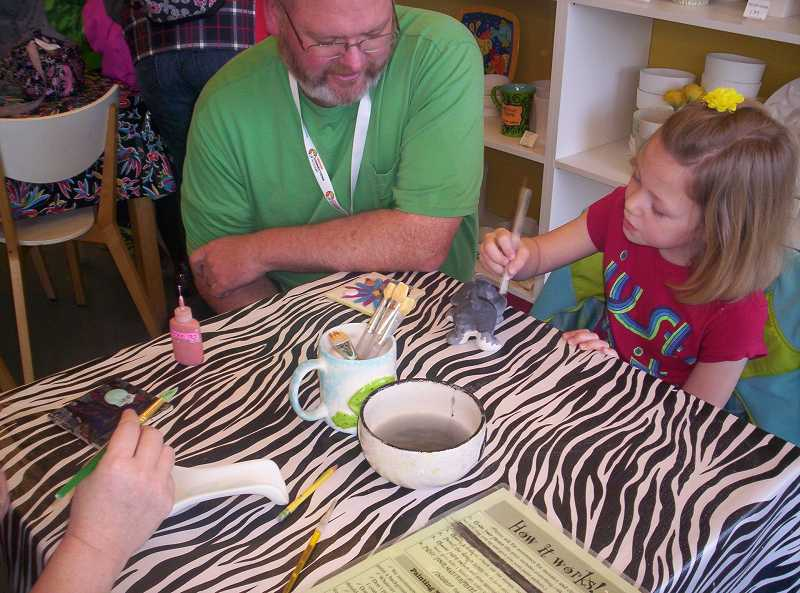 by: SUBMITTED PHOTO: LAUREN DILLON - Beaverton teacher Mark Duncan watches first-grader Addysen Behring, also from Beaverton, paint colorful glaze on her ceramic dog during the Oregon Connections Academy Cares Day event March 20 at Ceramicafe in Murrayhill. Several families and teachers from the statewide virtual public charter school brought items to benefit local food banks.