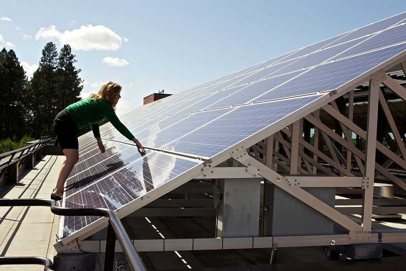 by: TIMES PHOTO: JAIME VALDEZ - Cindy Dolezel, sustainability manager with the city of Beaverton, scales solar panels atop the Beaverton City Library, which she helped get installed. The panels are one of the more visible signs of the city's support of renewable energy sources, which Portland General Electric recently recognized with an award.