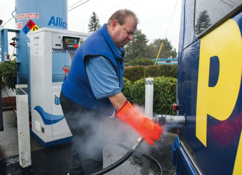 by: TRIBUNE PHOTO: JOHN VINCENT - A puff of propane is released as Park, Shuttle 'n Fly driver David Martin finishes refueling a propane Autogas-powered shuttle bus at the102nd and Prescott  Blue Star Gas facility. The small amount of propane released dissipates quickly into the air.
