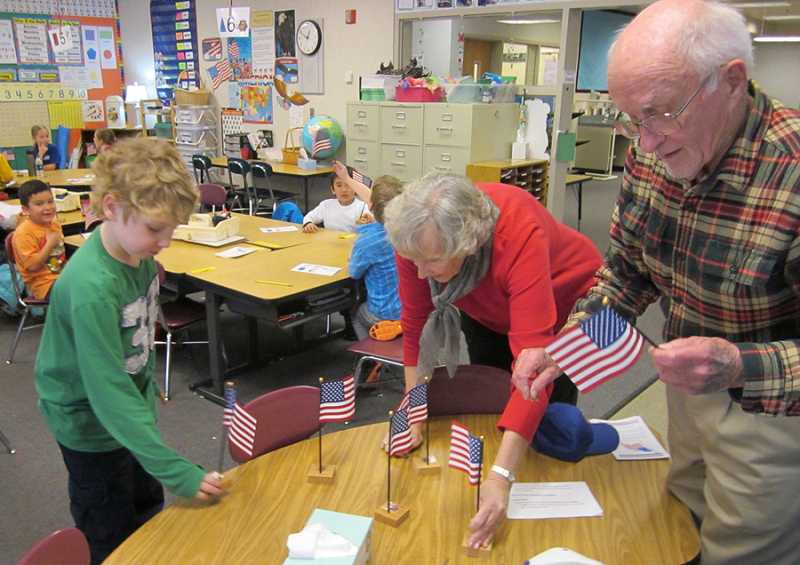 by: BARBARA SHERMAM - PATRIOTIC AND PROUD - Students in Tammy Estrada's first-grade class proudly hold the flags they have just received, while King City Lions Janie Berry of Newberg and Rupert Fixott of the Highlands place flags in stands before handing the rest of them out.