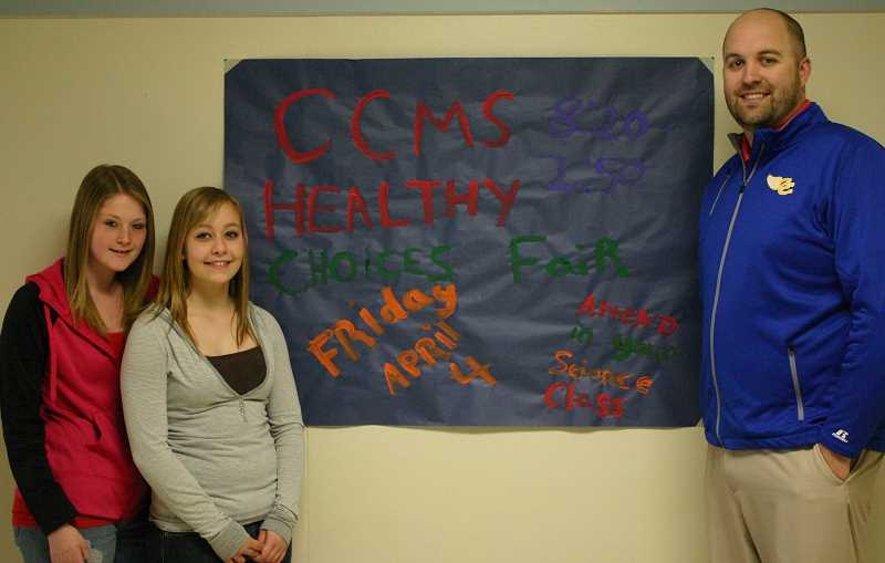 by: JASON CHANEY - From left, Miranda Slack, Megan Frost and CCMS principal Kurt Sloper display a poster advertising the health fair that will take place this Friday at the Crook County Middle School.