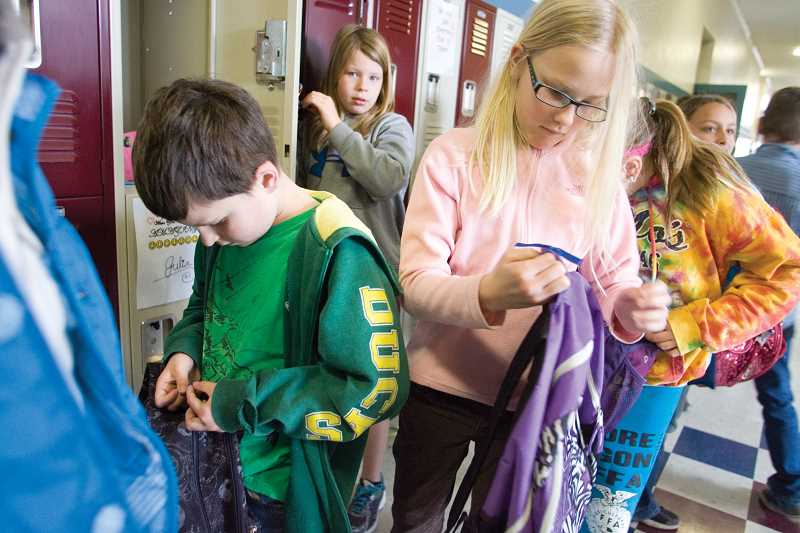 by: KEVIN SPERL - TOP: Crooked River fourth-grader Zachary Frantz ties a blue ribbon to his backpack. ABOVE: Fourth-graders Julia Mapes (RIGHT) and Brayden Baertlein tie blue ribbons to their backpacks in recognition of Child Abuse Prevention Month.
