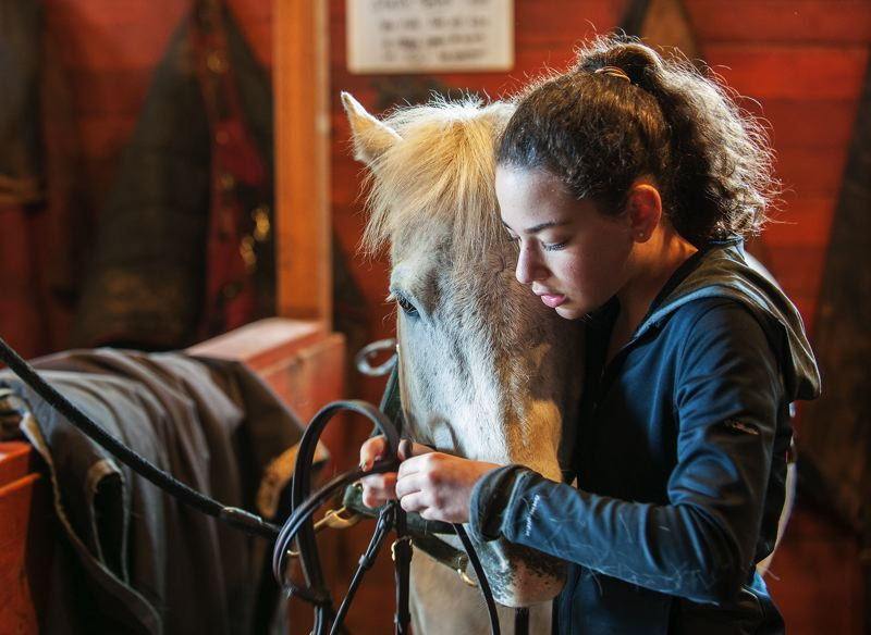 by: SPOKESMAN PHOTO: JOSH KULLA - Audrey Minch prepares her horse for a training session at Big Dog Stables outside Oregon City.