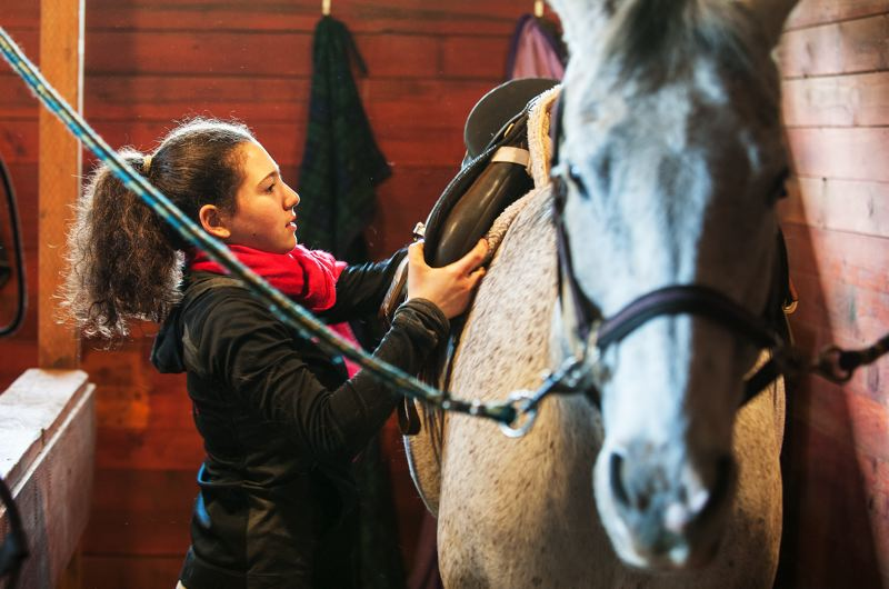 by: SPOKESMAN PHOTO: JOSH KULLA - Abigail Minch prepares her horse for a training session at Big Dog Stables outside Oregon City.
