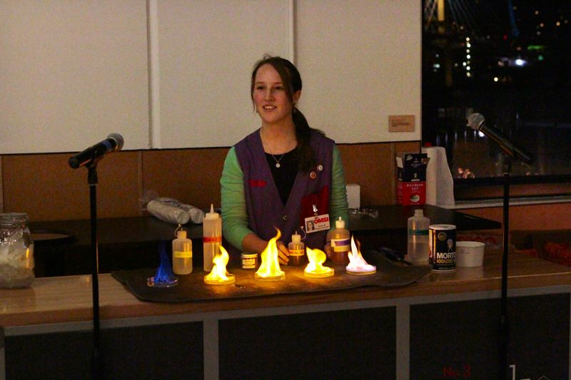 by: DAVID F. ASHTON - OMSI Food Science Educator Hayley Mauck shows how dissimilar salts burn with different colors.
