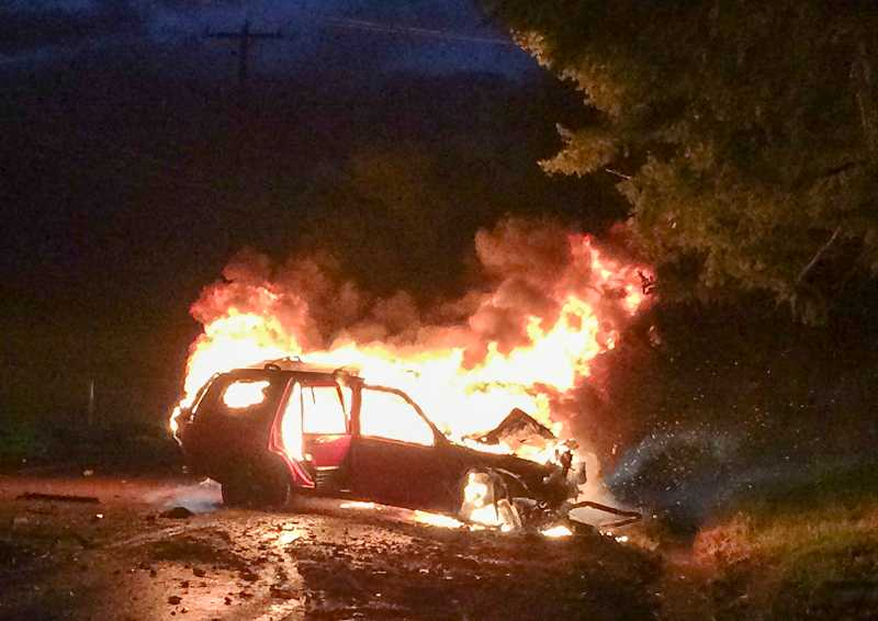 by: COURTESY PHOTO: MEGAN ROGERS - This photo was taken about 30 seconds after Nick Kingston and Washington County Sheriffs Cpl. Cheryl Crecelius pulled the unconscious driver from this burning Jeep Cherokee.
