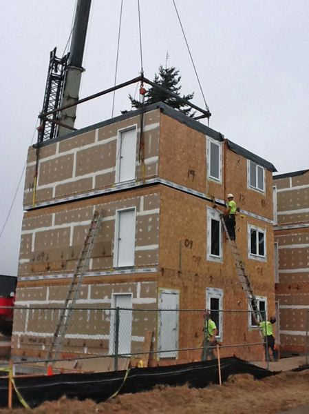 by: PHOTO COURTESY: NATIVE AMERICAN YOUTH ASSOCIATION - Construction workers oversee the stacking of pre-fabricated modules into the Kah San Chako Haws apartment building in Southeast Portland. The nine-unit development is an experiment in quicker and cheaper construction of low-income housing.