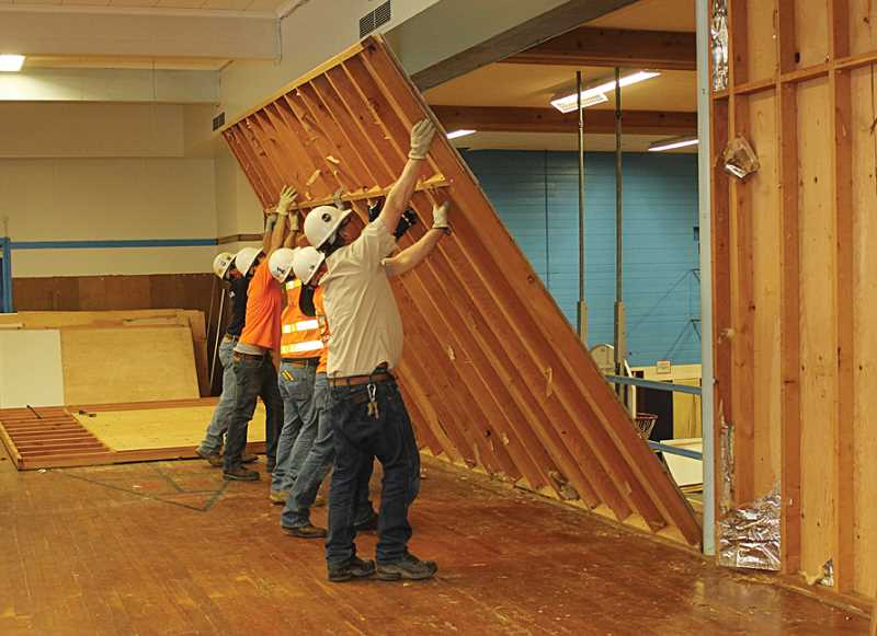 by: SUSAN MATHENY - Volunteers from the Skanska construction firm take down an upstairs wall at Westside to open the Kids Club's recreation room to the gym below. Removing the wall also improved ventilation in the upper gym.
