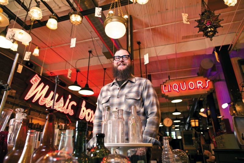 by: TRIBUNE PHOTO: JAIME VALDEZ - Nigel Barnes is used to being surrounded by unusual signs, light fixtures and assorted other house parts--hes the manager of salvage and antique lighting for Rejuvenation Inc. on Southeast Grand Ave.
