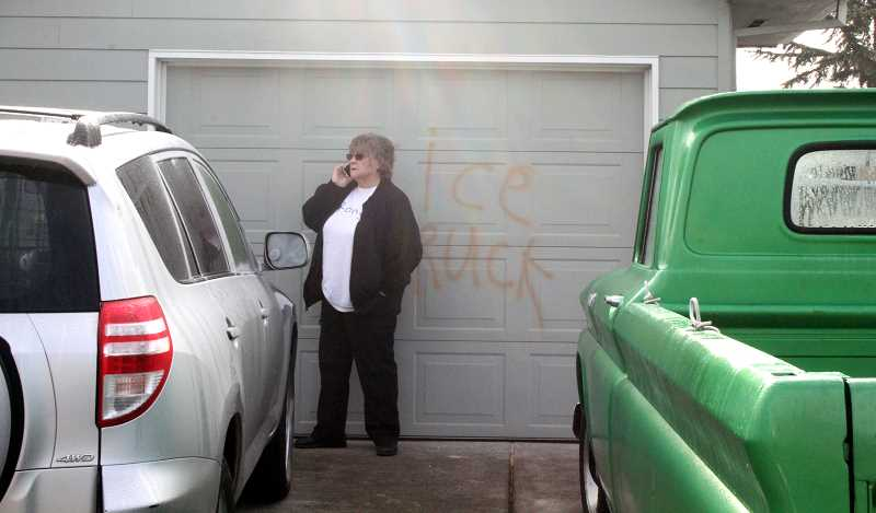 by: TYLER FRANCKE | WOODBURN INDEPENDENT - Paula Kilgore, a resident on Oregon Way in Woodburn, talks on her cellphone near her vandalized home and SUV Wednesday morning