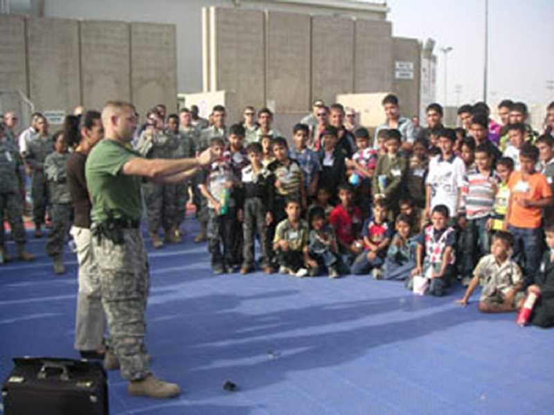 by: SCOTT ANDERSON - Anderson entertains children and troops with Operation Magic while serving in Iraq.
