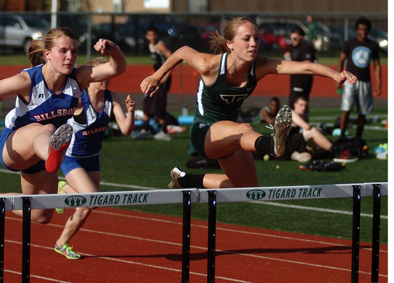 by: DAN BROOD - HURDLES HERO -- Tigard High School senior Lindsay Rosette (right), shown here in a meet from the 2013 season, looks to be one of the top hurdlers in the state this season.