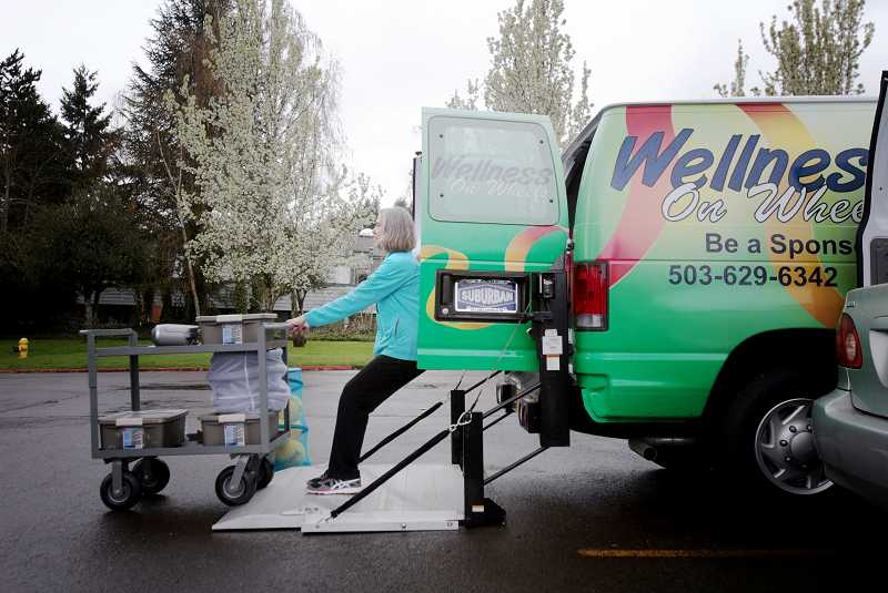 by: TIMES PHOTO: JONATHAN HOUSE - Lynn Robbin, fitness instructor for Wellness on Wheels, loads the W.O.W. van with exercise equipment she uses in classes at Holly Tree Village and Bethlehem Lutheran Church in Aloha.