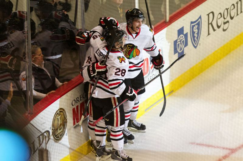 The Hawks celebrate Nic Petan's first-period goal.