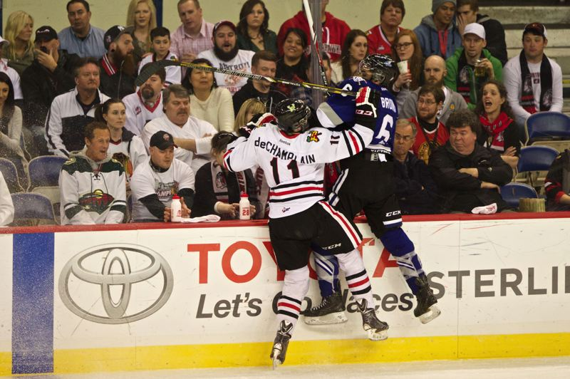 Portland's Adam de Champlain pushes Travis Brown of Victoria along the boards.