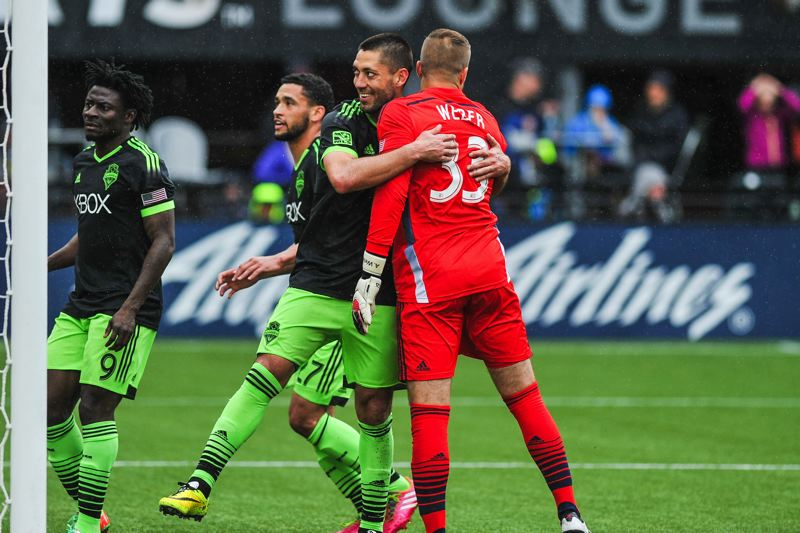 by: COURTESY OF JOHN LARIVIERE - Seattle's Clint Dempsey gives a playful hug to Portland goalkeeper Andrew Weber after scoring a goal in the 85th minute that pulled the Sounders to within 3-2 against the Timbers.
