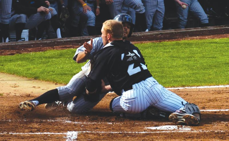 by: SANDY POST: PARKER LEE - Mt. Hood CC catch Louis Wolf tags out a Lane runner at the plate during last weeks split with the Titans.