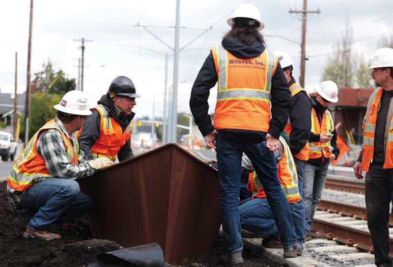 by: TRIBUNE PHOTO: JONATHAN HOUSE - Artist and sculptor Bill Will, second from left, consults with TriMet crews about the placement of his metal boat sculptures that sit along the new light-rail line in Southeast Portland.