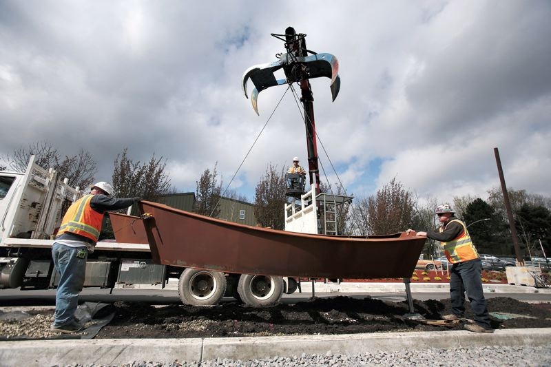 by: TRIBUNE PHOTO: JONATHAN HOUSE - TriMet crews begin lowering metal boat sculptures along the new Portland-Milwaukie light-rail line on Southeast 17th Avenue.