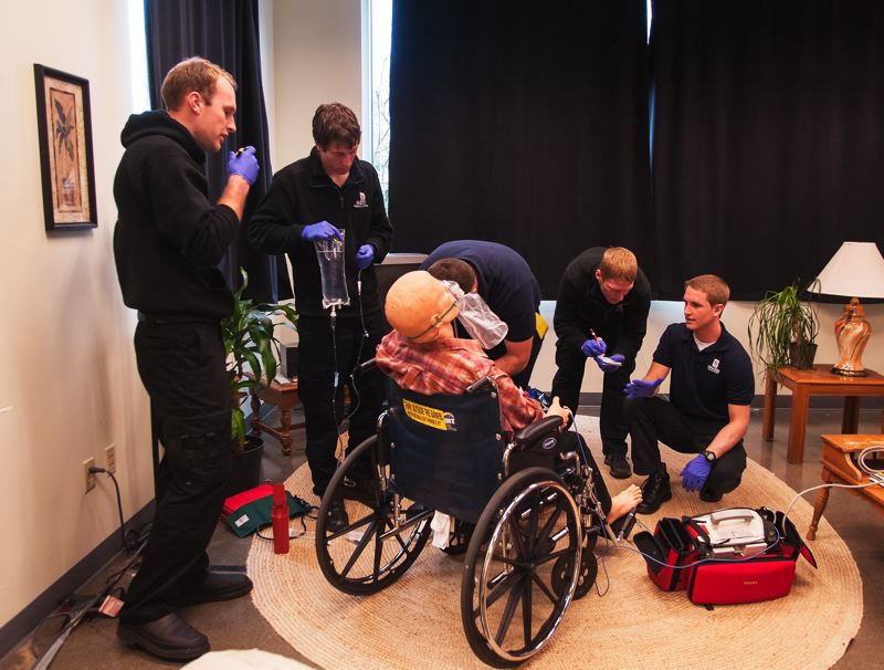 by: SPOKESMAN PHOTO: JOSH KULLA - Oregon Tech paramedic students respond to a simulated patient suffering from chest pain. Here, the patient in the wheelchair sits in his living room on the Oregon Tech Wilsonville campus as the students work on him.