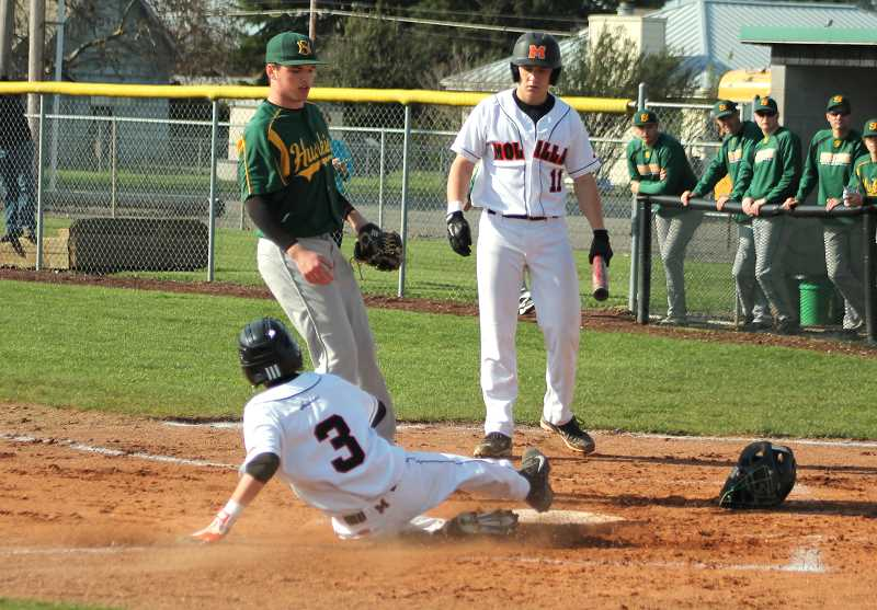 by: CORY MIMMS - Kurt Potter slides into home.