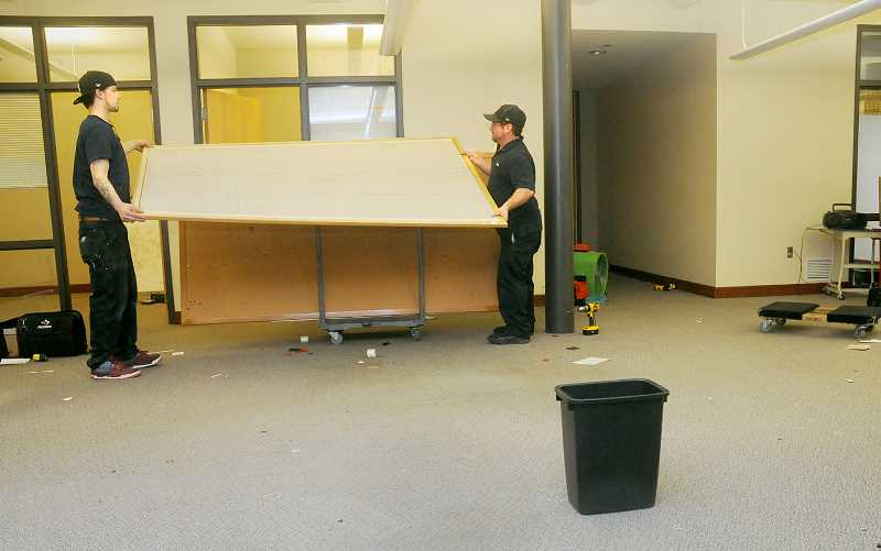 by: GARY ALLEN - Rebuilding -- Workers from the DWI Company of Oregon remove cubicles and furniture preparing the City Hall basement for repairs after the flood March 28.
