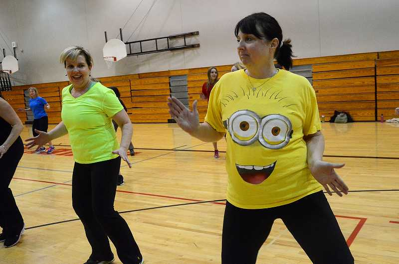by: TIDINGS PHOTO: VERN UYETAKE - Kathy Versteef, left, and Denise Zanner get their zumba on at the fundraiser to benefit Wilsonville High Schools Unified Sports program.
