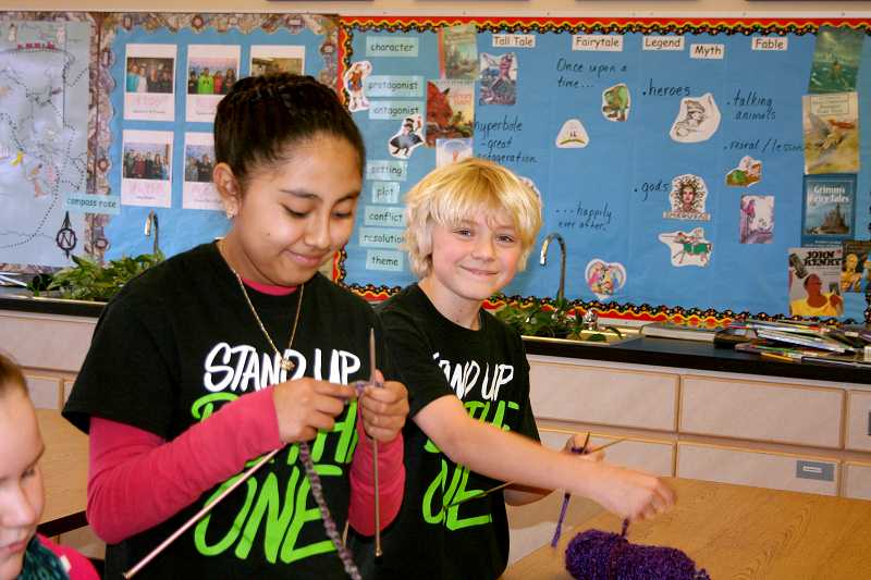 by: PAMELA THOMAS - Molalla River MIddle School Sixth-graders Yuleimi Maldonado and Max Kavanagh work on their knitting with donated yarn Friday. It was Max's mother, Kerry Kavanagh who bought the skein of yarn that had the $100 'Benny Bill' tucked inside it.