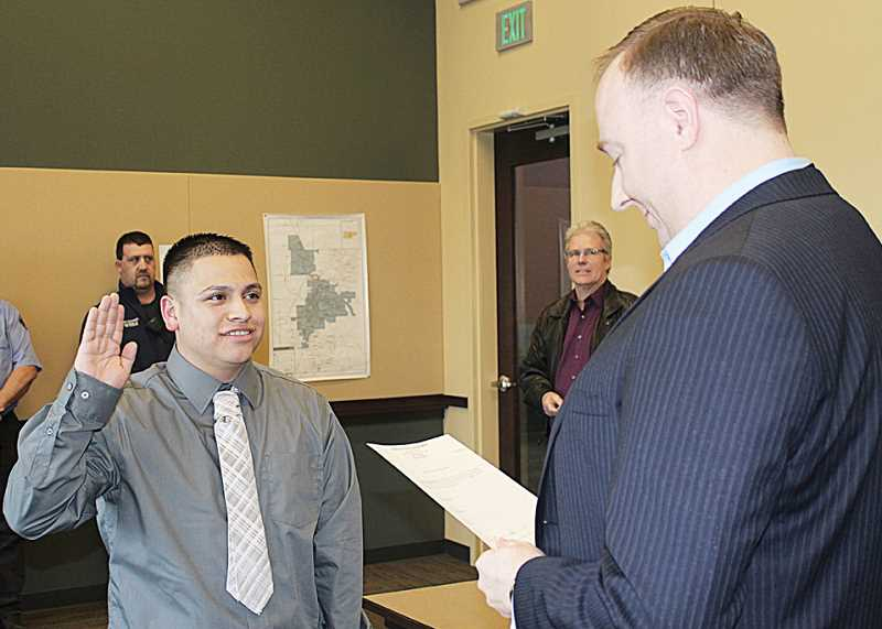 by: HOLLY M. GILL - Charlie Villanueva, 23, left, is the Madras Police Department's newest reserve officer. City Administrator Gus Burril swore Villanueva in on April 2, at the new police station. Police Chief Tom Adams is at right, behind Burril.
