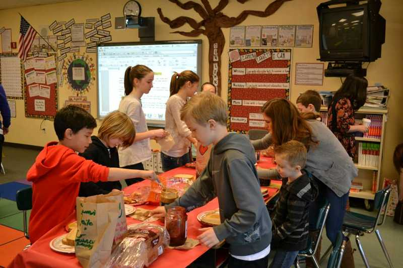 by: CONTRIBUTED PHOTO - Students in Terri Buckley's third-grade class at Findley Elementary School prepare 'Smile Bags,' organic-food lunches in paper sacks they adorn with their artwork, on Friday, April 4.