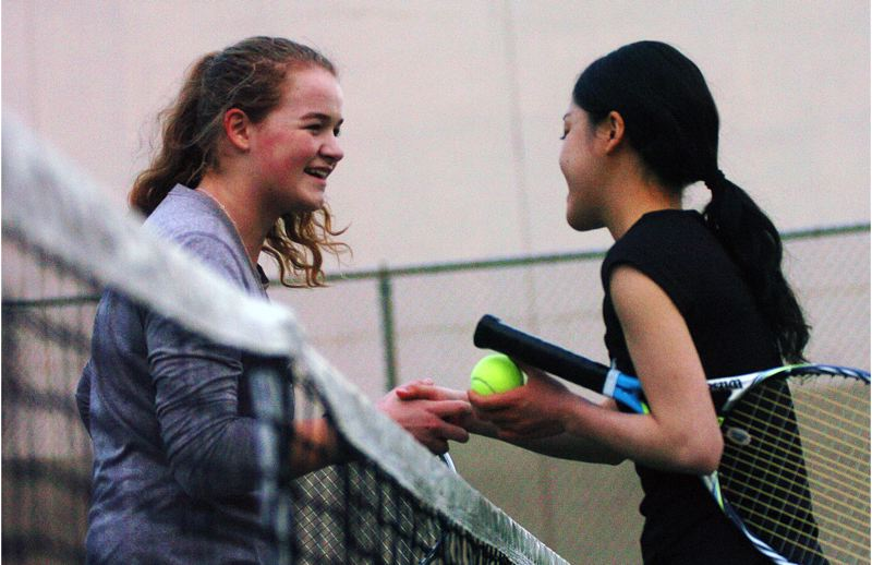 by: DAN BROOD - GOOD MATCH -- Tigard senior Courtney Roshak (left) and Tualatin junior Ayumi Mizuno meet at the net following their No. 1 singles contest.